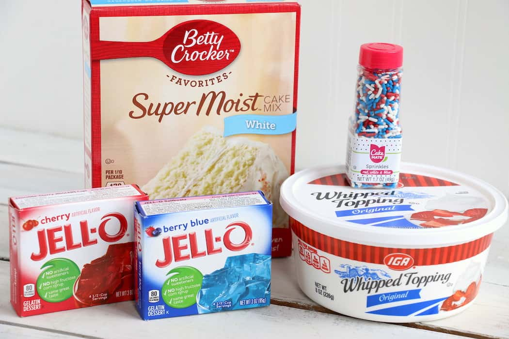 Show your American pride with this Patriotic Jello Poke Cake! Moist, delicious cake drizzled with sweet, colorful jello, all covered with whipped topping! #InspirationalMomma #jellopokecake #pokecake #America #4thofJuly #jello #cake #dessert #desserts #recipe #patriotic #redwhiteblue
