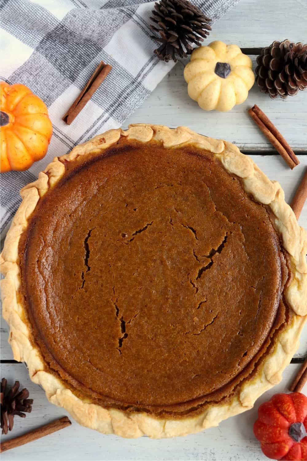 A full pumpkin pie surrounded by pine cones, pumpkins, and cinnamon sticks.