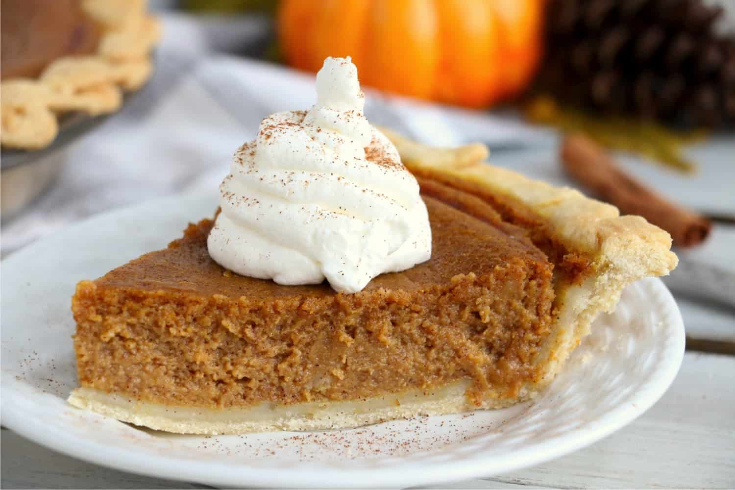 A piece of pumpkin pie on a white plate, surrounded by fall decorations.