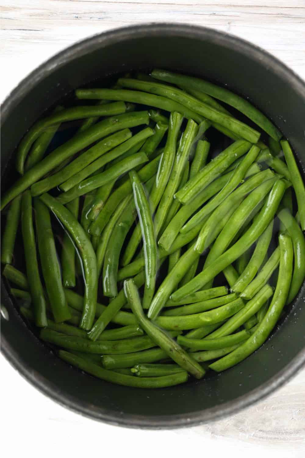 Green beans in water, cooking in a pot on the stove