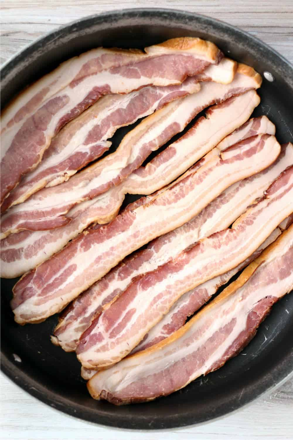 Strips of bacon cooking in a skillet