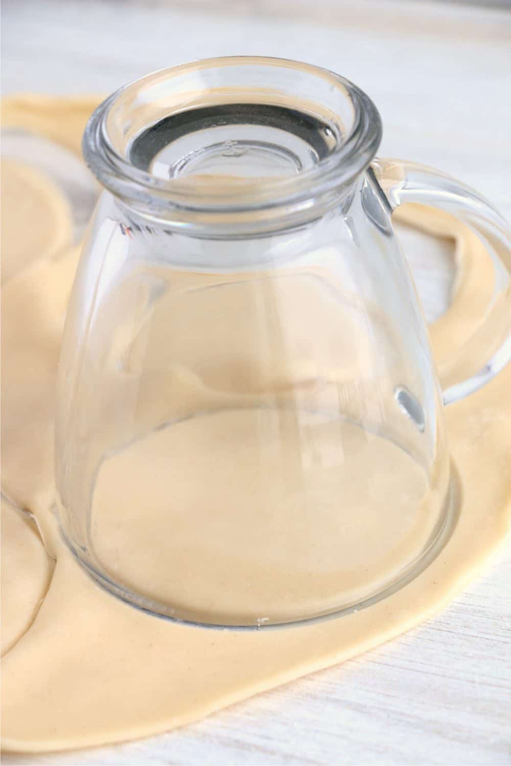 A clear glass being used to cut pie crust circles.