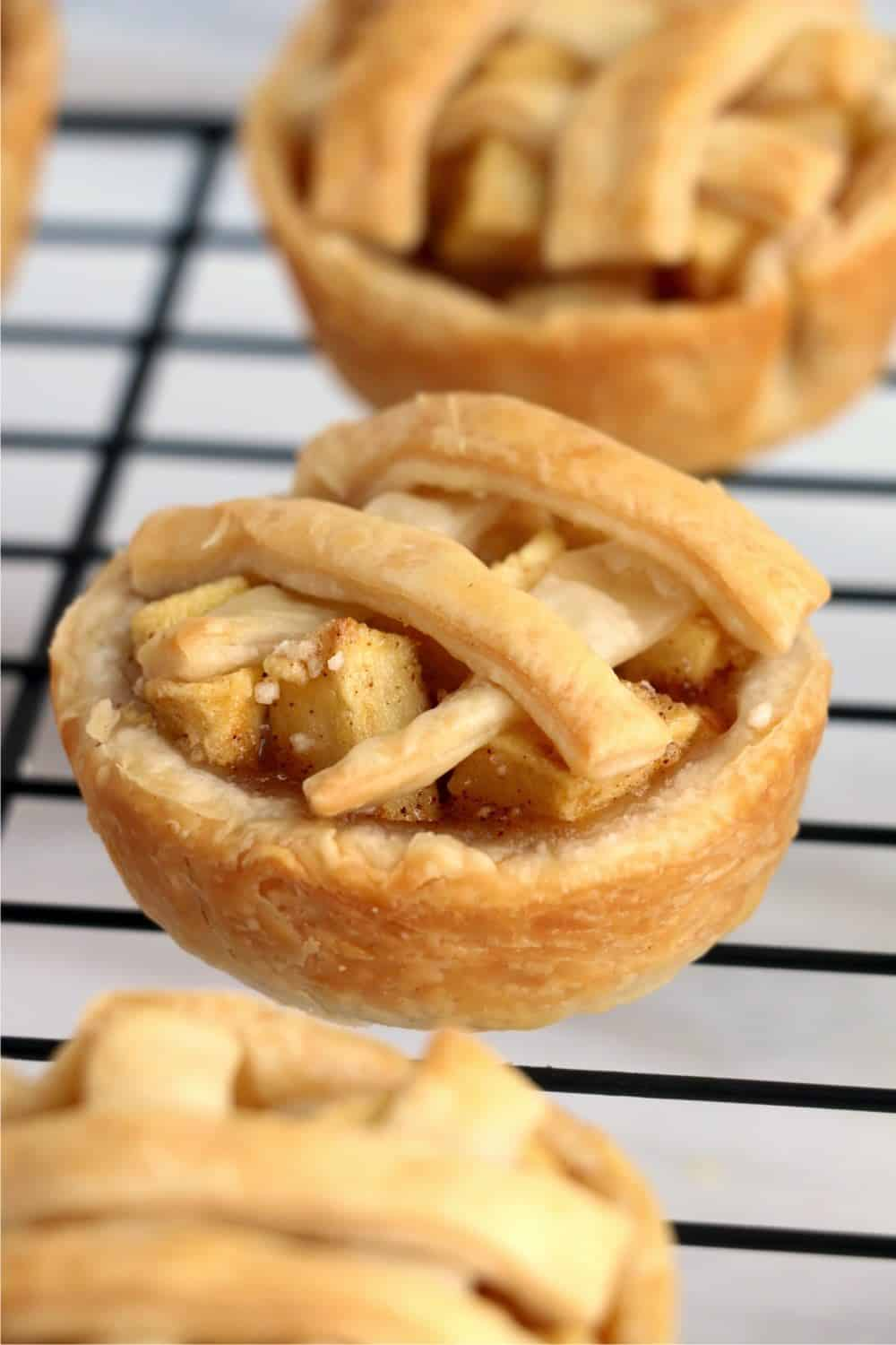 Mini apple pies cooling on a baking rack