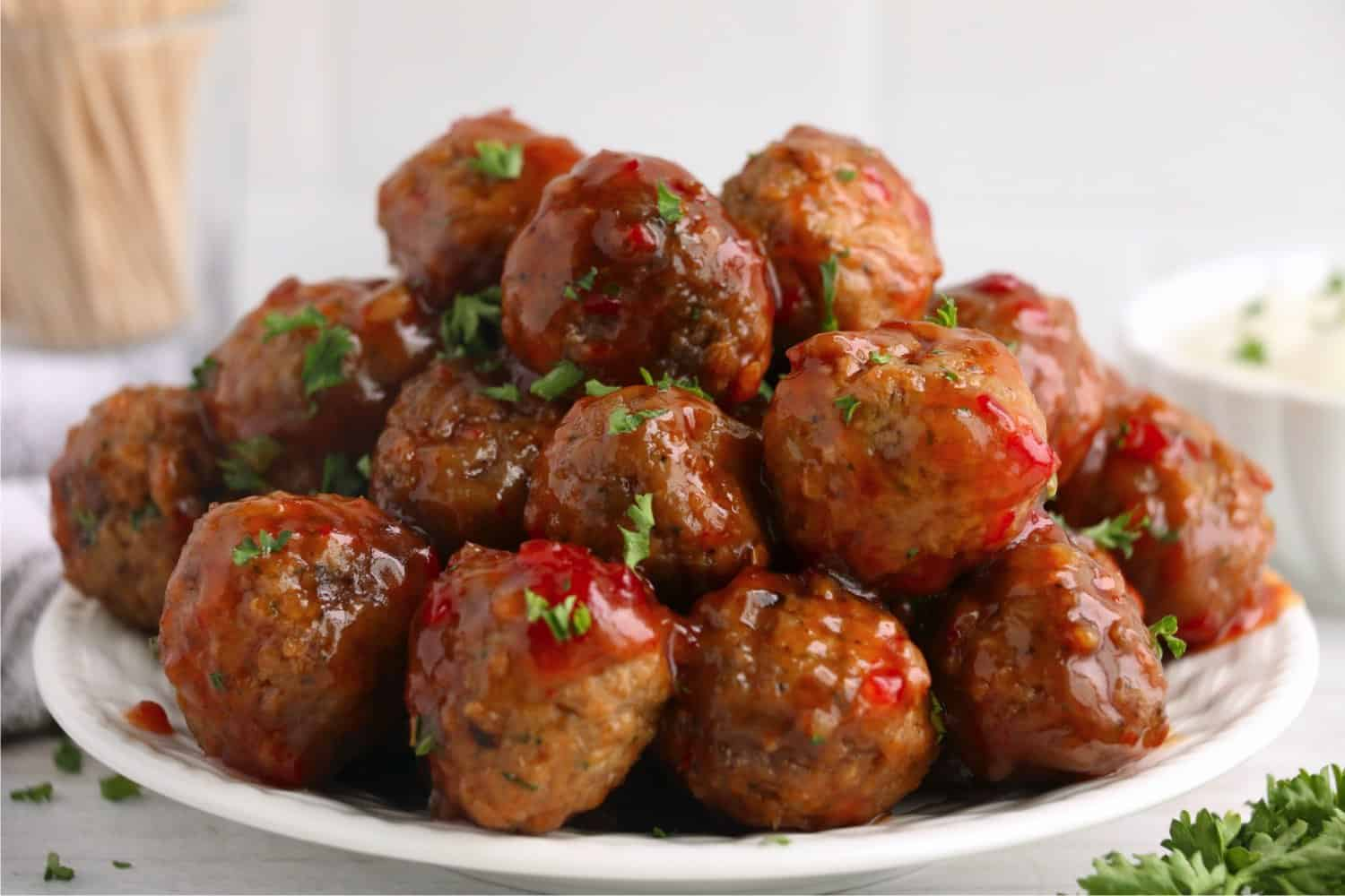 A pile of cooked sweet chili meatballs lightly garnished with parsley, ready to be eaten.