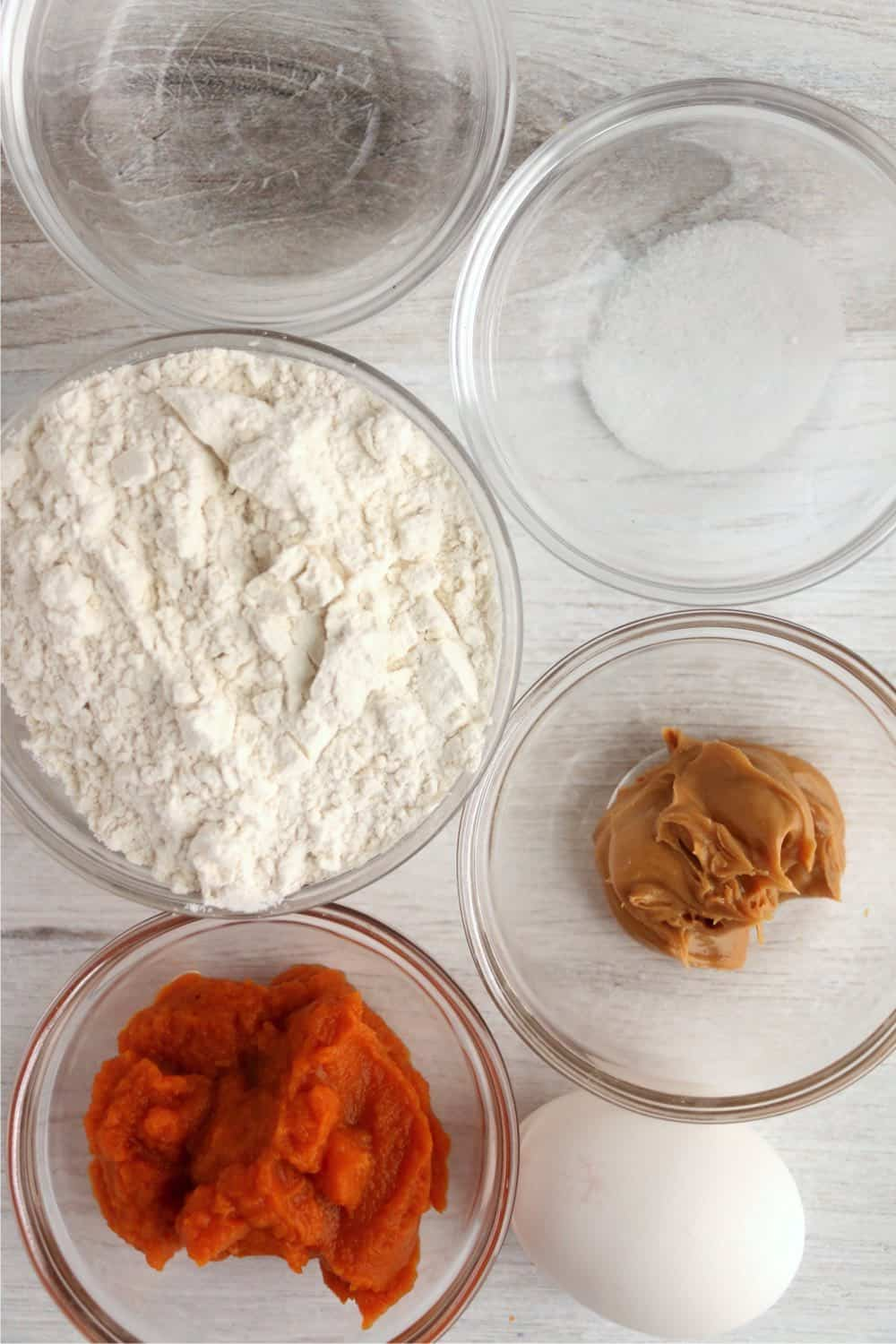 bows with recipe ingredients including flour, pumpkin, peanut butter, egg, salt, water