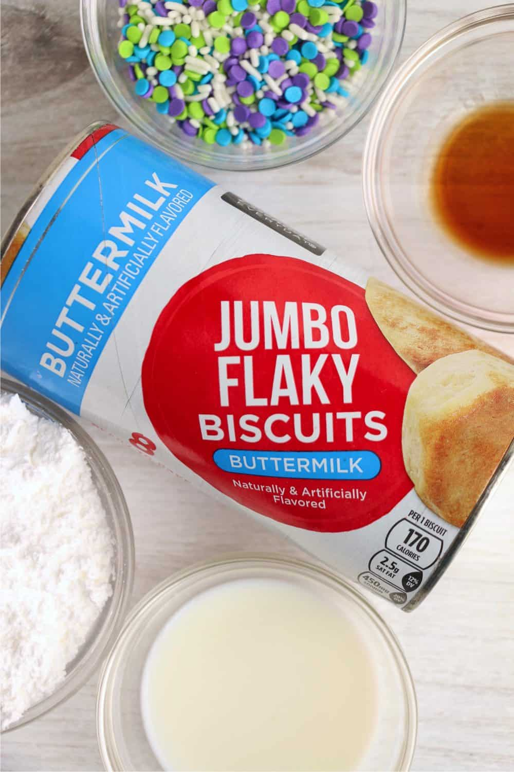 Ingredients for air fryer donuts from buscuits: refrigerated biscuits, powdered sugar, milk, vanilla, sprinkles