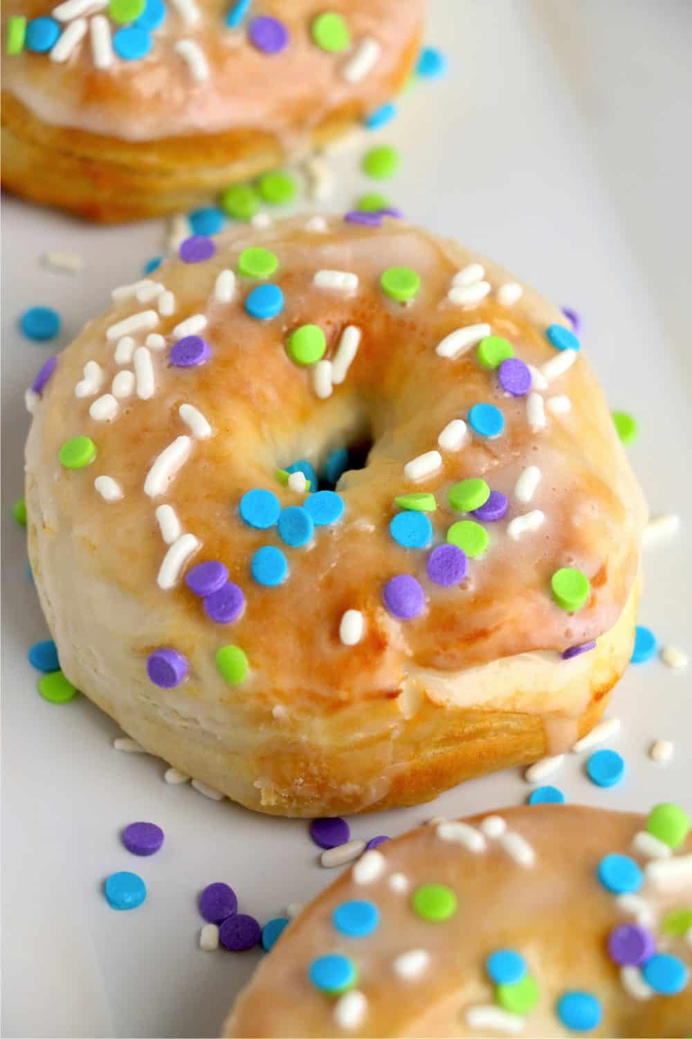 a close-up shot of a biscuit donut with icing and sprinkles