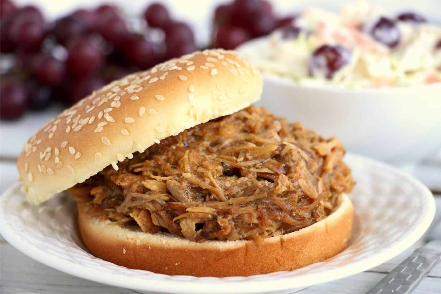 A delicious-looking hamburger bun with pulled pork made in a slow cooker on a plate