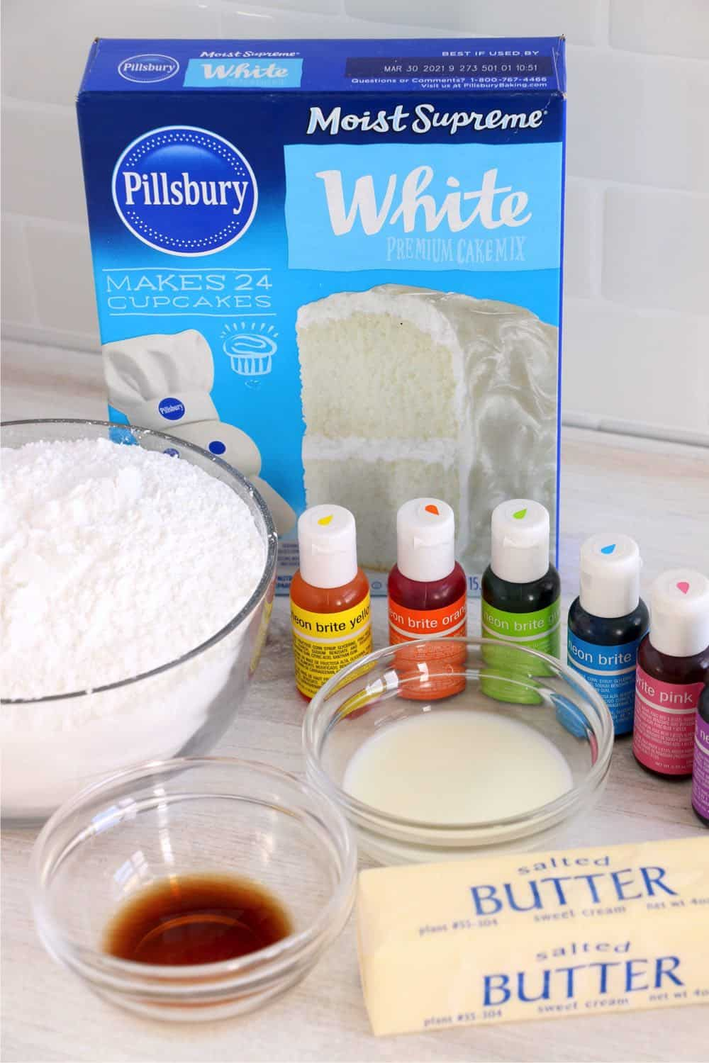 Photo of ingredients for this recipe including cake mix, food coloring, butter, vanilla, powdered sugar and milk