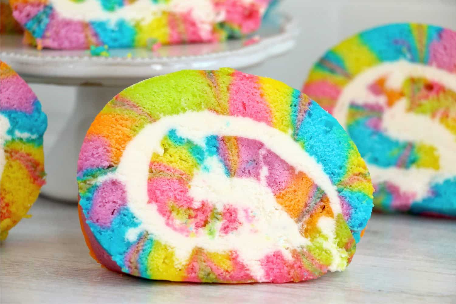 This Tie Dye Vanilla Cake Roll is a sweet, rich, and decadent roll cake filled with homemade buttercream frosting. Perfect for parties!