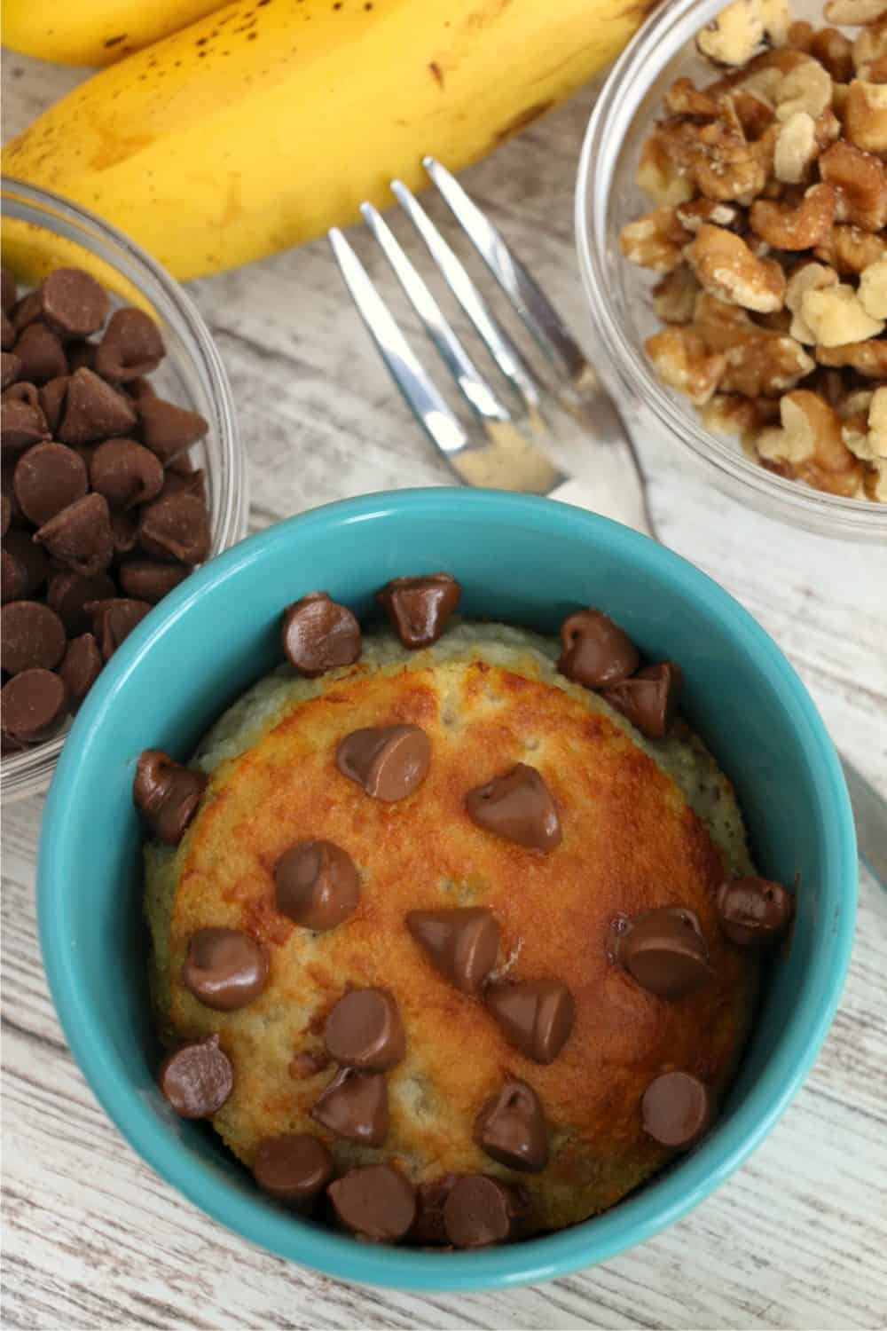 A tight overhead shot of freshly-baked banana mug cake with chocolate chips sprinkled on top and starting to melt. A fork is on the table near the mug, as well as a bowl of chocolate chips, a bowl of chopped walnuts and a banana