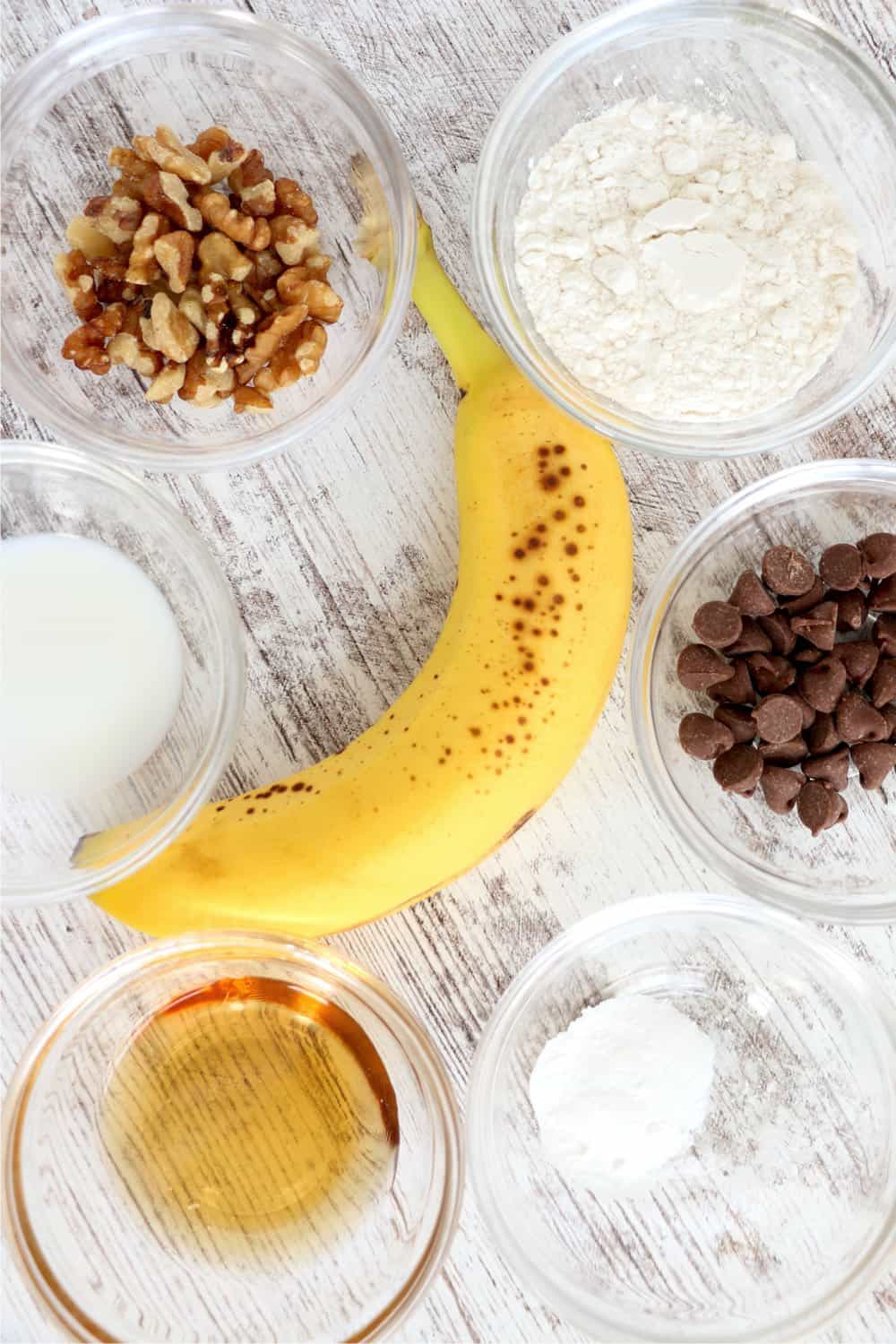 A banana in its peel surrounded by clear bowls filled with walnuts, flour, milk, maple syrup, baking powder and chocolate chips