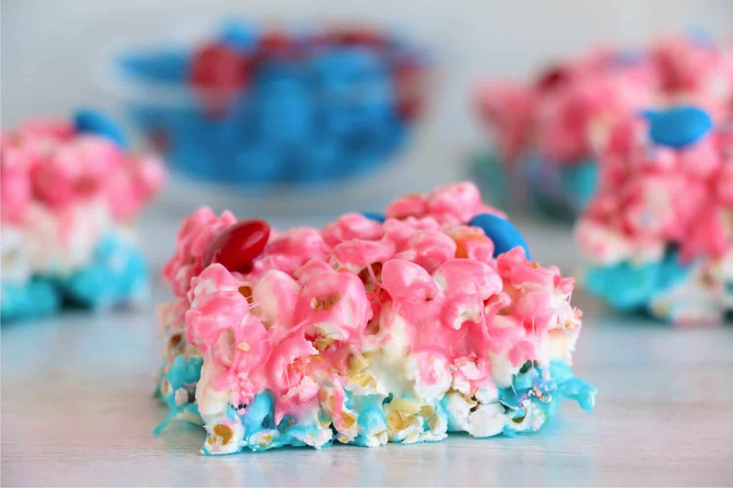 A piece of red, white, and blue popcorn cake is in focus in the foreground while other pieces of cake are displayed in a checkboard pattern in the blurry background