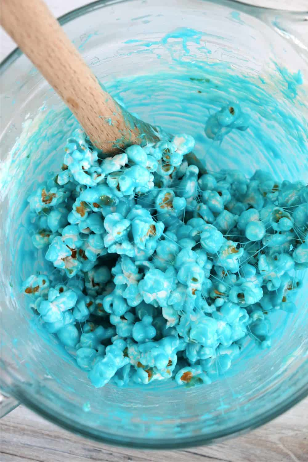 Stirring the popcorn in blue dyed melted marshamllows