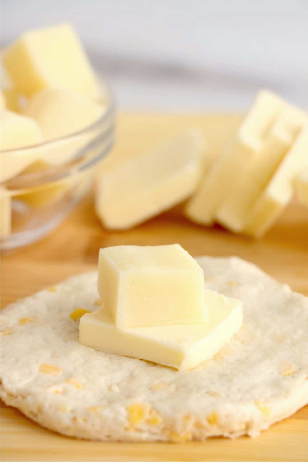 Butter and cheese in the middle of raw biscuit dough