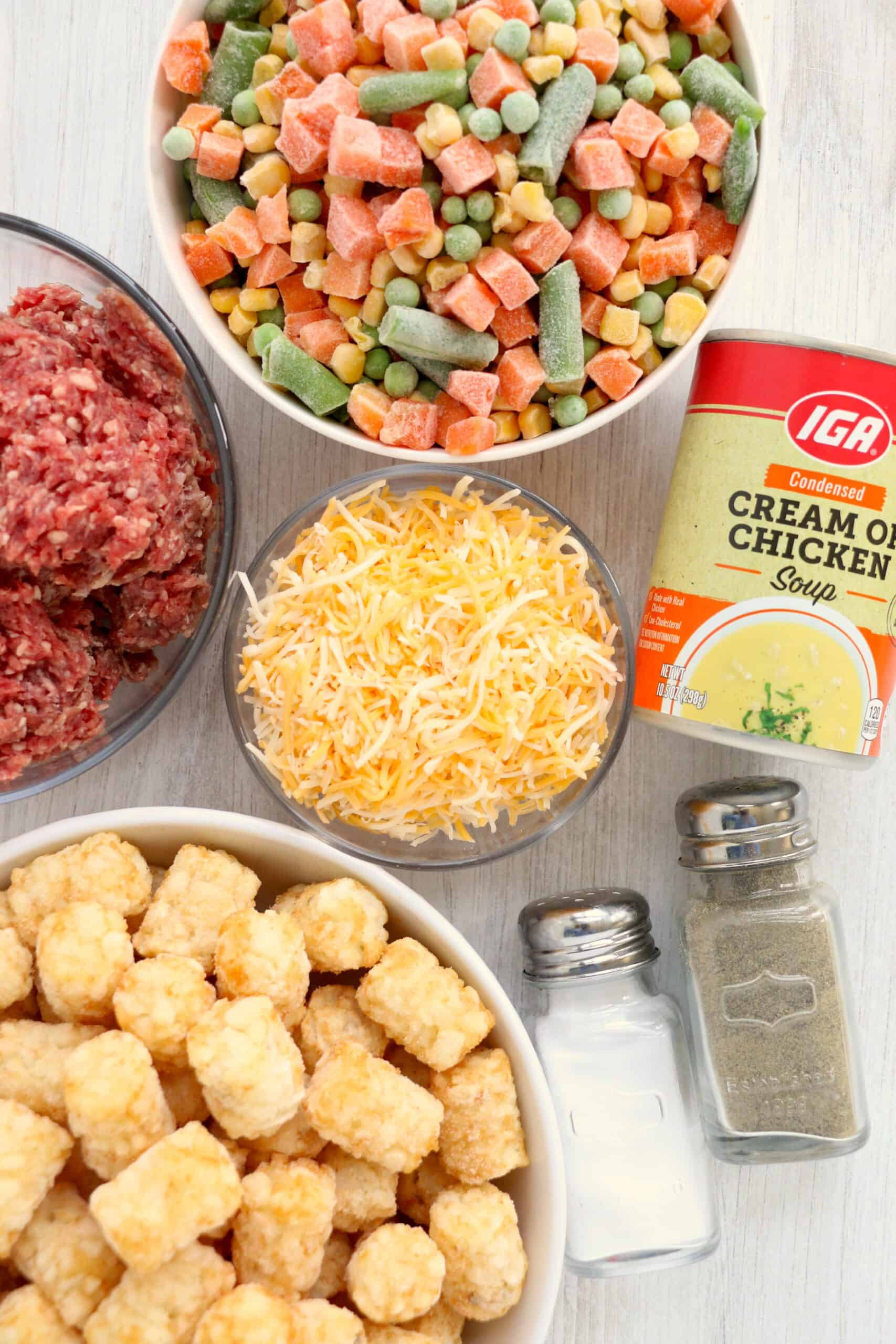 bowls of raw ground beef, frozen mixed vegetables, can of cream of chicken soup, shredded cheese and tater tots. Also a salt and pepper shaker in the bottom right hand side.