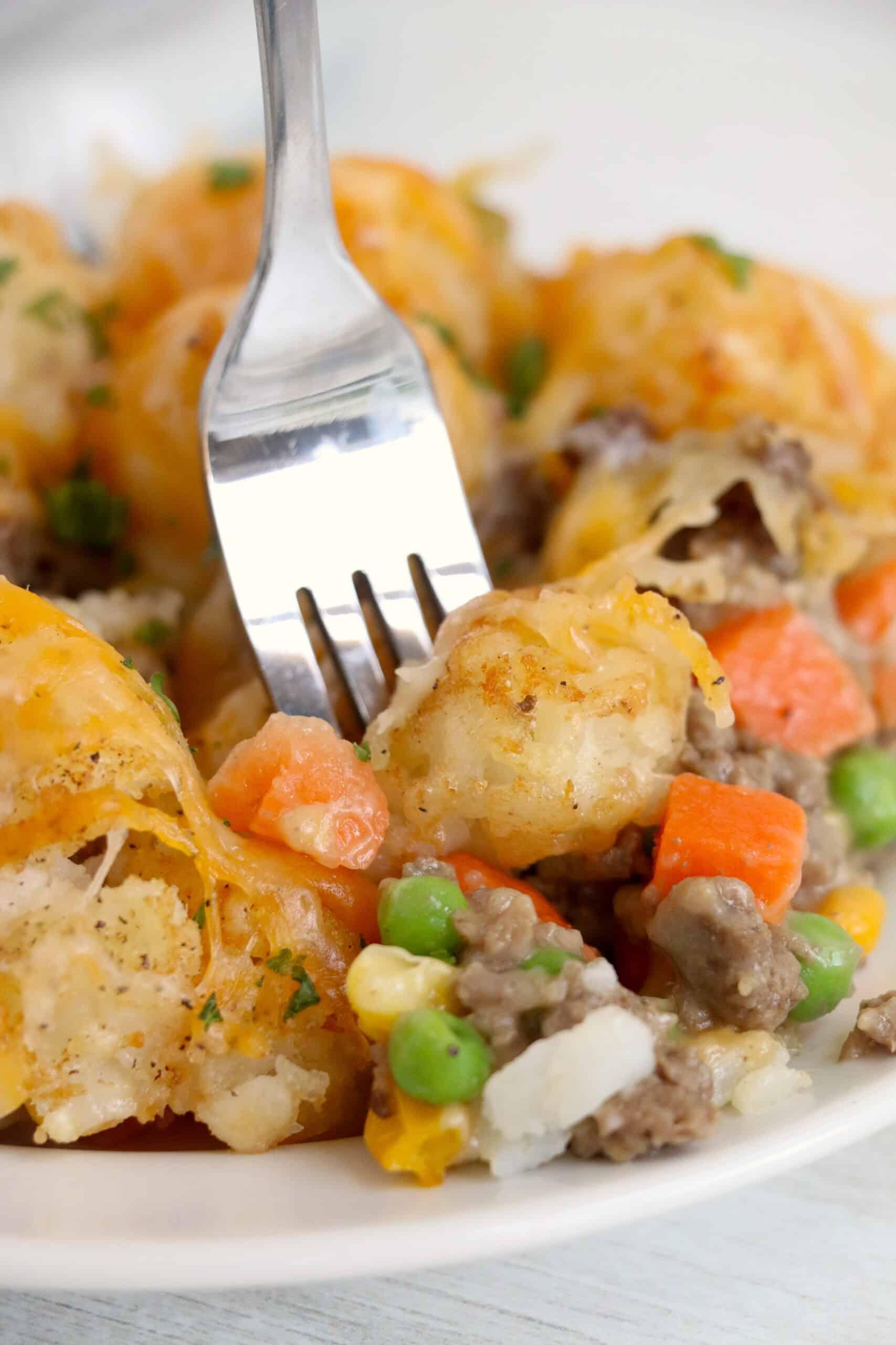 close up of Ninja Foodi Tater Tot Casserole with sliver fork inside.