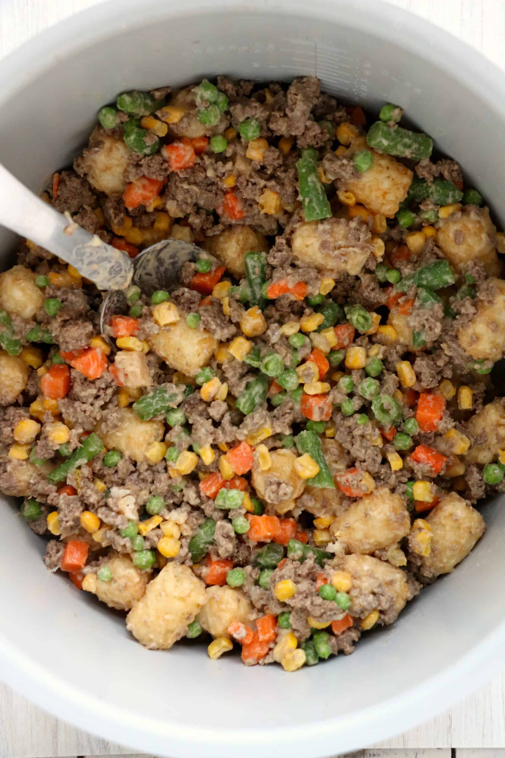 ground beef, frozen mixed vegetables, tater tater tots in a mixing bowl.