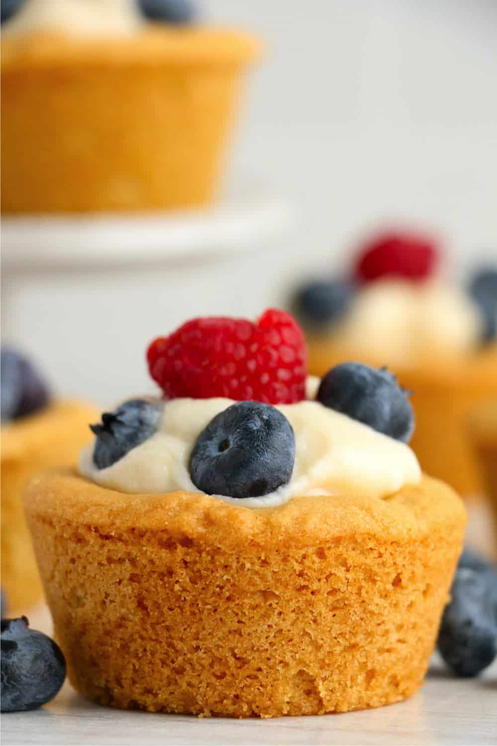 zoomed in image of a sugar cookie cups filled with cheesecake and topped with fresh berries.